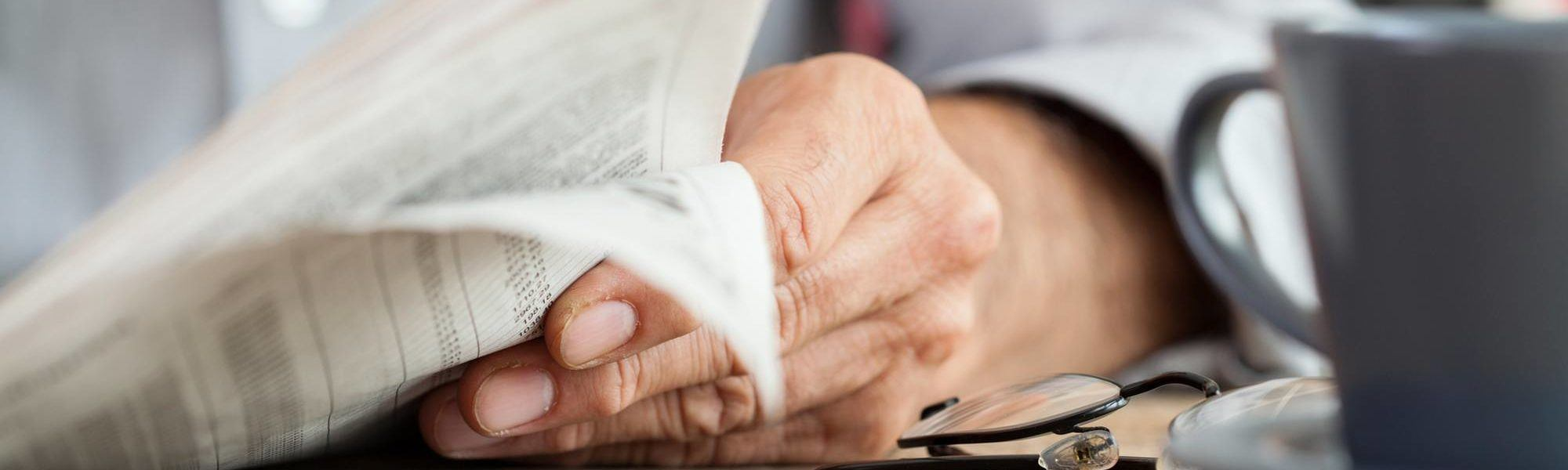 Hand holding the newspaper resting on a table with a cup of coffee